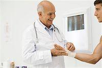 Doctor bandaging patient's wrist Stock Photo - Premium Royalty-Freenull, Code: 695-05771249