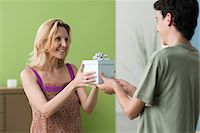 Teenage son presenting gift to mother Stock Photo - Premium Royalty-Freenull, Code: 695-05771312
