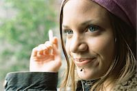 Young woman with facial piercing, smoking, close-up Stock Photo - Premium Royalty-Freenull, Code: 695-05772249