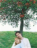 sitting under tree - Couple sitting under tree listening to earphones, portrait Stock Photo - Premium Royalty-Freenull, Code: 695-05772441