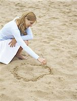 Woman drawing circle in sand, portrait Stock Photo - Premium Royalty-Freenull, Code: 695-05772442