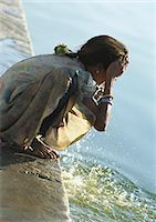 India, Sarkej, girl washing face by river Stock Photo - Premium Royalty-Freenull, Code: 695-05772504
