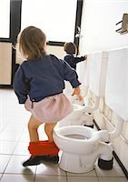 Little girl next to children's toilet with panties around ankles, rear view, other toilets and child in background. Stock Photo - Premium Royalty-Freenull, Code: 695-05772878