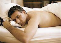 Man lying on stomach in bed, elbow out, eyes closed, waist up Stock Photo - Premium Royalty-Freenull, Code: 695-05773051