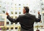 Businessman standing in front of building, arms raised in victorious gesture, rear view Stock Photo - Premium Royalty-Free, Artist: Arcaid, Code: 695-05773233