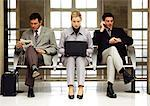 Businesswoman using laptop sitting between two businessmen. Stock Photo - Premium Royalty-Free, Artist: Cultura RM               , Code: 695-05773237