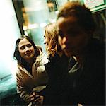 Three young women sitting in bus shelter at night, close-up Stock Photo - Premium Royalty-Free, Artist: KL Services, Code: 695-05773263
