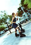 Mature woman and young girl in-line skating, blurred