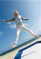 fitness   mature woman - Mature woman jumping on trampoline at the beach, arms out, legs spread Stock Photo - Premium Royalty-Freenull, Code: 695-05773391