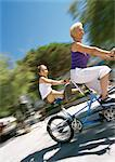 Mature woman and girl riding tandem bike, granddaugher sticking her legs out, blurred