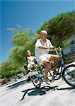 Mature man and girl riding tandem bike, granddaughter with legs out, blurred motion
