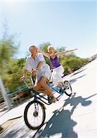 fitness   mature woman - Mature couple riding together on tandem bike, woman holding her arms out, blurred Stock Photo - Premium Royalty-Freenull, Code: 695-05773395