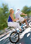 Mature man and woman riding together on tandem bike, blurred