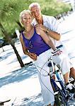 Mature man and woman posing on stationary bike, portrait
