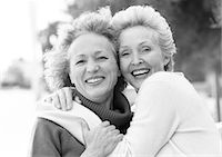 Two mature women smiling at camera, one with arms around the other's shoulders, portrait, B&W Stock Photo - Premium Royalty-Freenull, Code: 695-05773447