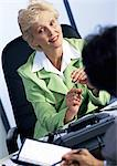 Businesswoman listening to colleague, blurred foreground Stock Photo - Premium Royalty-Free, Artist: Robert Harding Images, Code: 695-05773659