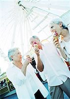 Retired friends eating ice cream in amusement park Stock Photo - Premium Royalty-Freenull, Code: 695-05773678