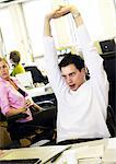 Man stretching in office, colleagues in background Stock Photo - Premium Royalty-Freenull, Code: 695-05773719