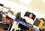Man sitting with feet on desk, eyes closed Stock Photo - Premium Royalty-Free, Artist: Transtock, Code: 695-05773737