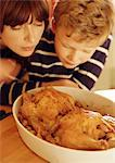 Woman and child looking at chickens in casserole dish Stock Photo - Premium Royalty-Free, Artist: Transtock, Code: 695-05773767