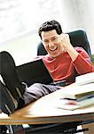 Man with laptop on lap and feet on desk, smiling Stock Photo - Premium Royalty-Free, Artist: Transtock, Code: 695-05773863