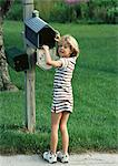 Girl with hand in mailbox, looking into camera Stock Photo - Premium Royalty-Freenull, Code: 695-05773923