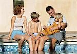 Young family sitting together, feet in pool (frontal view). Stock Photo - Premium Royalty-Freenull, Code: 695-05773946