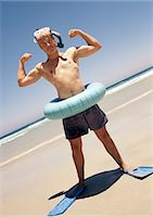 Man wearing snorkeling gear and inner tube, flexing at the beach. Stock Photo - Premium Royalty-Freenull, Code: 695-05773949