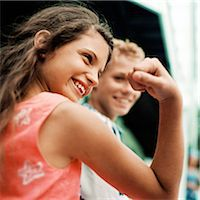 Girl flexing arm muscles, boy in background, smiling Stock Photo - Premium Royalty-Freenull, Code: 695-05774098