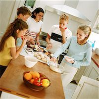 Young people snacking around table in kitchen Stock Photo - Premium Royalty-Freenull, Code: 695-05774112