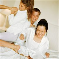 Young people playfighting on bed, smiling Stock Photo - Premium Royalty-Freenull, Code: 695-05774116