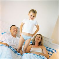 Girl standing between parents on bed Stock Photo - Premium Royalty-Freenull, Code: 695-05774224