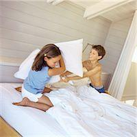 Children having pillow fight in bed Stock Photo - Premium Royalty-Freenull, Code: 695-05774229