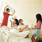 Family having pillow fight on bed Stock Photo - Premium Royalty-Free, Artist: Rick Gomez, Code: 695-05774245