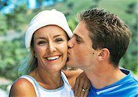 Teenage boy kissing mature woman's cheek, close-up, portrait Stock Photo - Premium Royalty-Freenull, Code: 695-05774361