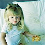 Girl sitting on bed, holding croissant Stock Photo - Premium Royalty-Freenull, Code: 695-05774385