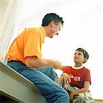 Father and son sitting, low angle view Stock Photo - Premium Royalty-Free, Artist: Kevin Dodge              , Code: 695-05774497