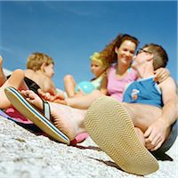 Couple and children on beach, focus on man's feet in foreground Stock Photo - Premium Royalty-Freenull, Code: 695-05774500