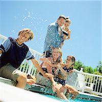 Family splashing water at edge of swimming pool Stock Photo - Premium Royalty-Freenull, Code: 695-05774536