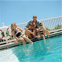 Family sitting at edge of swimming pool Stock Photo - Premium Royalty-Freenull, Code: 695-05774537