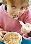 Little girl eating cereal, looking into camera, portrait. Stock Photo - Premium Royalty-Freenull, Code: 695-05774774