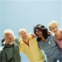 Two men and two women arms around each others' shoulder laughing and smiling Stock Photo - Premium Royalty-Freenull, Code: 695-05774827