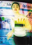 Young woman holding credit card toward camera, digital composite. Stock Photo - Premium Royalty-Freenull, Code: 695-05775033