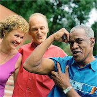 Three people standing outside, man flexing arm muscles Stock Photo - Premium Royalty-Freenull, Code: 695-05775149