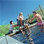 Three people trying to push a man into water Stock Photo - Premium Royalty-Free, Artist: Transtock, Code: 695-05775153