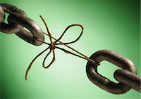 fragile - Two ends of a chain linked by string, close-up Stock Photo - Premium Royalty-Freenull, Code: 695-05775432