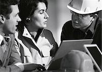 professional (pertains to traditional blue collar careers) - Three people with laptop computer, one with hard hat, head and shoulders, b&w Stock Photo - Premium Royalty-Freenull, Code: 695-05776099