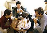 Three men in living room, two playing chess Stock Photo - Premium Royalty-Free, Artist: F1Online, Code: 695-05776158