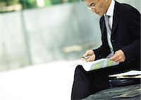 Businessman sitting outdoors, examining documents Stock Photo - Premium Royalty-Freenull, Code: 695-05776281
