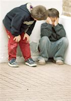 Two children in corner, one holding head Stock Photo - Premium Royalty-Freenull, Code: 695-05776431
